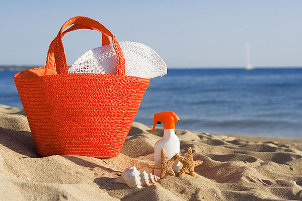 beach vacation gear - beach tote, straw hat, and suntan lotion plus seashells, sand, and surf