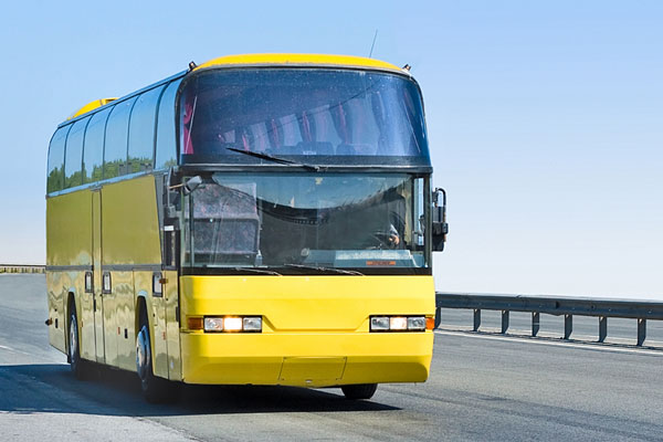 yellow bus traveling on highway