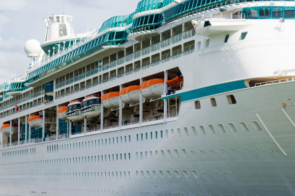 large cruise ship with passenger decks and lifeboats