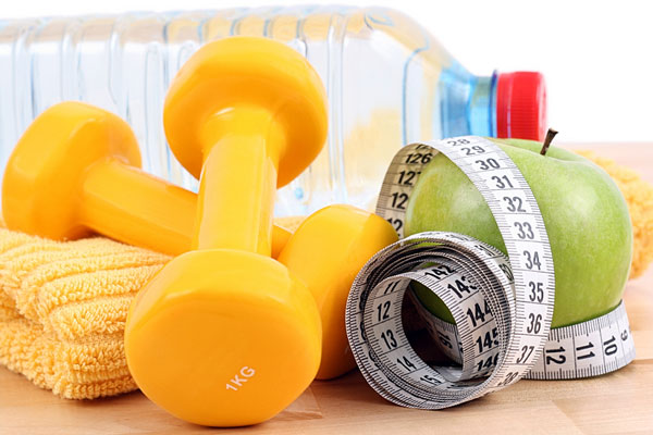 a measuring tape and dumbbells plus an apple and bottled water