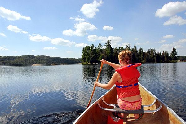 girl paddling a canoe